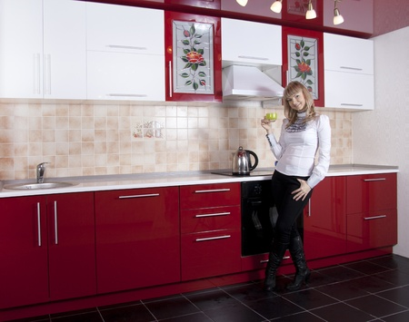 Young woman to kitchen in red-white color Stock Photo - 9226638