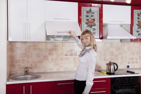 Young woman to kitchen in red-white color photo