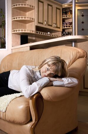 lain: Young woman has lain down to have a rest on a sofa