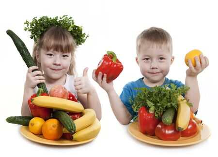 Vegetables and fruit it are a healthy food of children. Child holds different vegetables and fruit.