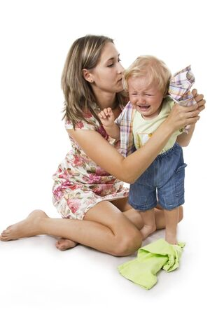crying child: Careful mother dresses the son. Isolated on white.