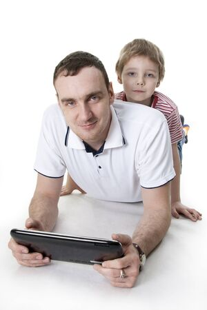 Father and son sitting on a floor with the computer on white isolation photo