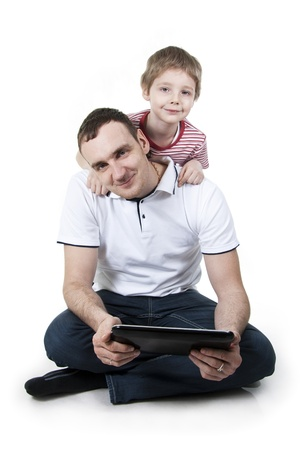father and son: Father and son sitting on a floor with the computer on white isolation