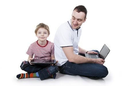 android tablet: Father and son sitting on a floor with the computer on white isolation