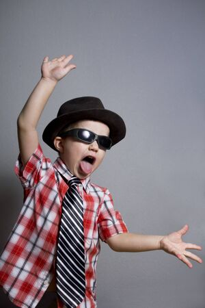 The boy in a hat and black glasses on a gray background photo