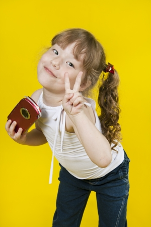 Little girl playing handheld portable game console. Yellow background photo