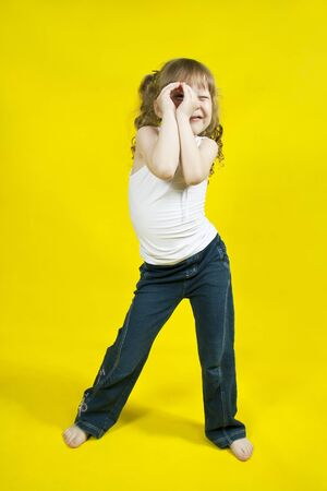 Cheerful girl dances on a yellow background photo