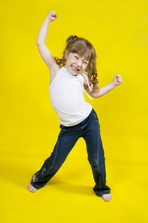 školačka: Veselá dívka tančí na žlutém pozadí Reklamní fotografie