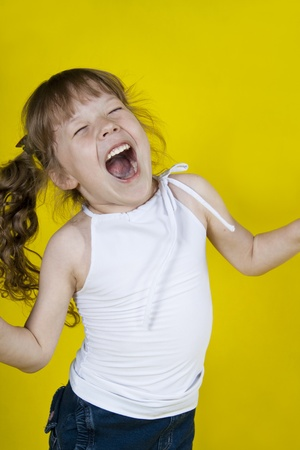 sings: Cheerful girl dances on a yellow background Stock Photo
