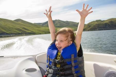 Zwei Kinder sitzen auf dem Bug eines Bootes mit Schwimmwesten gibt, die Spaß