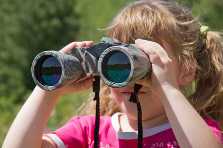 attentiveness: Child and nature. Environment supervision in the field-glass. Stock Photo