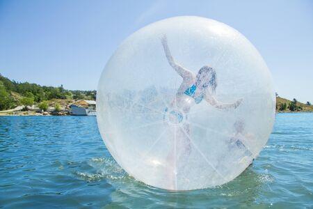 woman floating: Joyful children in a balloon floating on water.