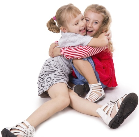 naughty child: Two fun girls of the girlfriend play. White isolated.