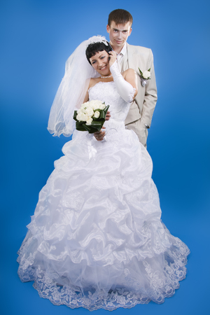 Loving groom and beautiful bride are happy together. Blue background. photo