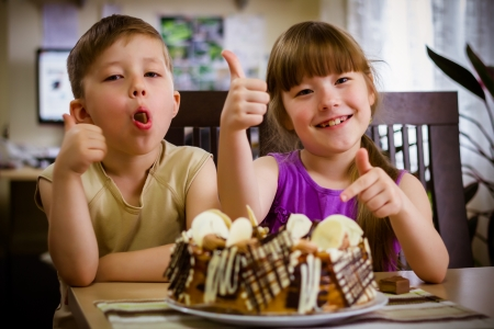 Children sit near a table and eat a cake photo