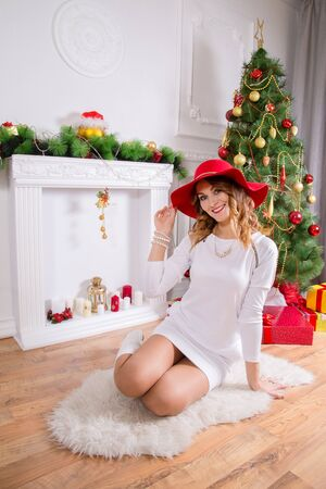 vestidos de epoca: Beautiful woman in a red hat and a white dress. Christmas scenery, sitting on a floor.