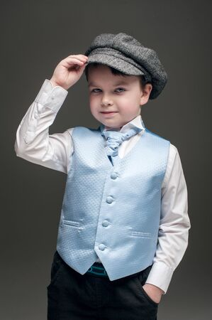 Little boy in cap and blue vest Stock Photo