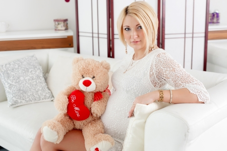 valentine s day teddy bear: pregnant girl hugging a teddy bear