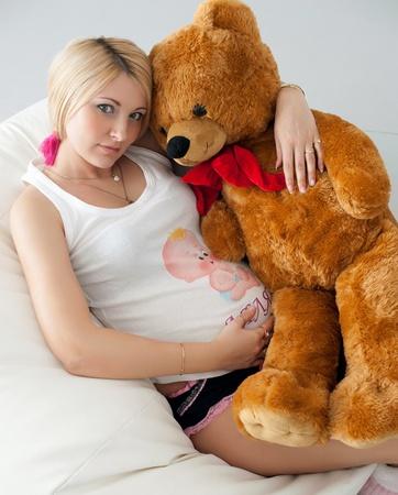 valentine s day teddy bear: pregnant girl hugging a teddy bear