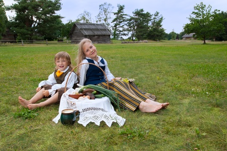 latvia girls: Little boy and girl sitting on a lawn in a national latvian clothes