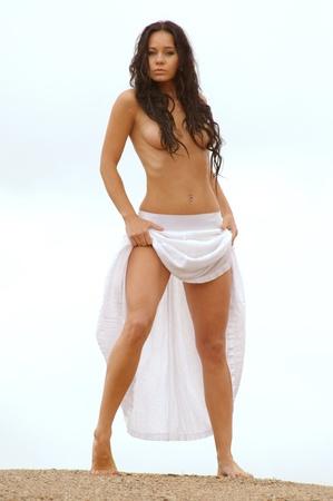 Topless brunette in white skirt walking on a sand