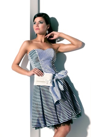 girl in a striped dress posing with a white bag in his hand
