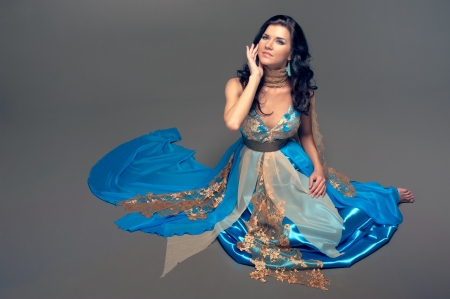 seeting: beautiful Indian girl in a blue dress sitting on the floor