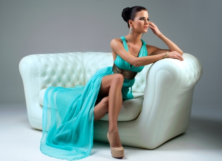 girl in a turquoise dress lying on sofa Stock Photo