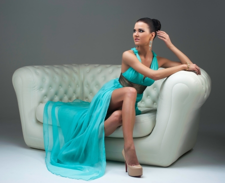 girl in a turquoise dress lying on sofa photo
