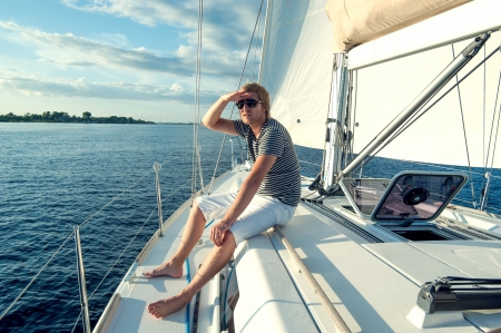 Happy young man on a yacht photo