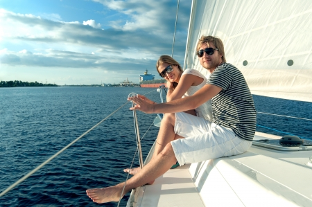 rich people: Happy young couple relaxing on a yacht Stock Photo