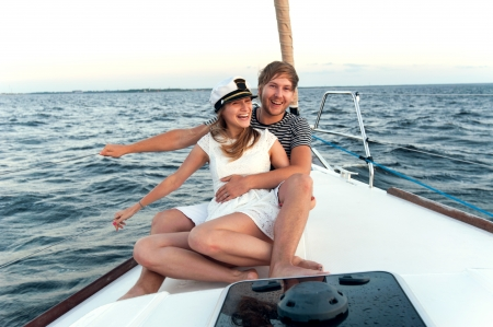 recreation yachts: Happy young couple relaxing on a yacht Stock Photo