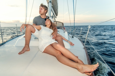 cruising: Happy young couple relaxing on a yacht Stock Photo