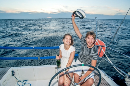 Happy young couple drinking champagne on yacht