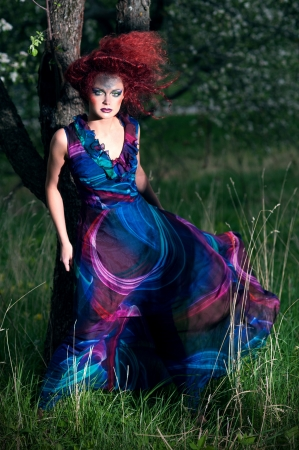 Woman in design hat and dress outdoors photo