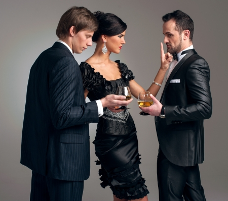 Two stylish men in suits and a girl in an evening black dress