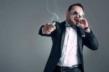Cool man in a suit with a cigar, gun and glass with alcoholic beverage photo