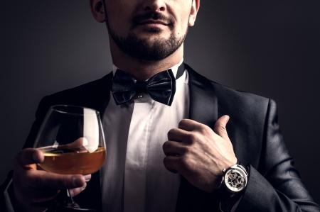 Cool man in a suit with a cigar, gun and glass with alcoholic beverage