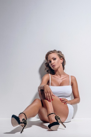 Young beautiful woman posing in white dress photo