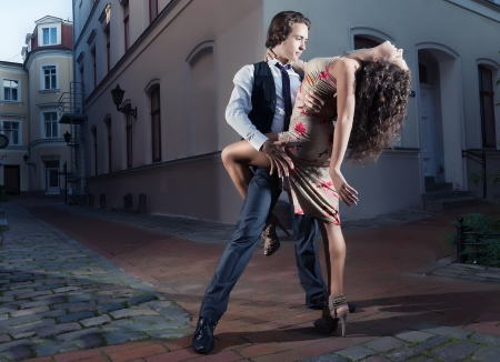 Young couple perform dance steps on the street photo