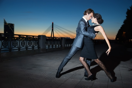 young couple dancing tango on the quay of the river city Riga, night photo