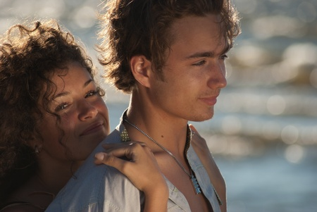 A young couple on the background of the sea at sunset, enjoying the weather photo