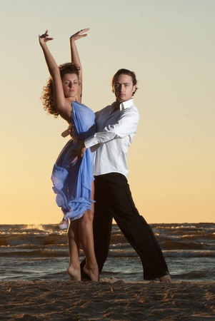young couple dancing tango on the beach photo