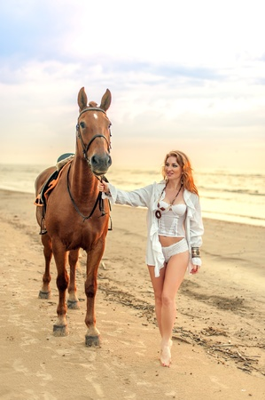 Young woman and horse on sea cost photo