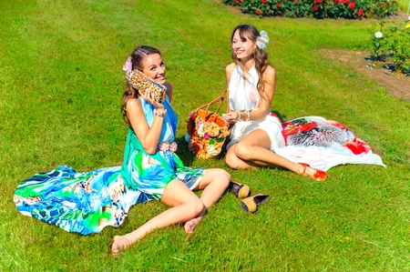 nice weather: two women in flowers park in summer dresses