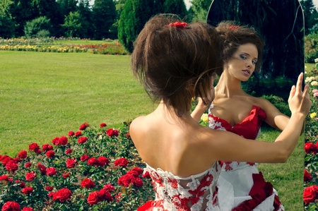 a beautiful young girl in a red dress look in the mirror photo