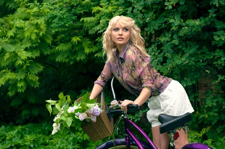 Beautiful young woman portrait with bicycle in the park  photo