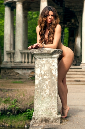 Naked girl standing near an old ruined house
