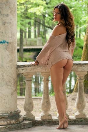 Beautiful sexy woman posing near an old ancient columns