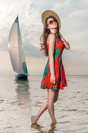 girl in a dress with poppy enjoys the surf against the backdrop of a sailing yacht photo